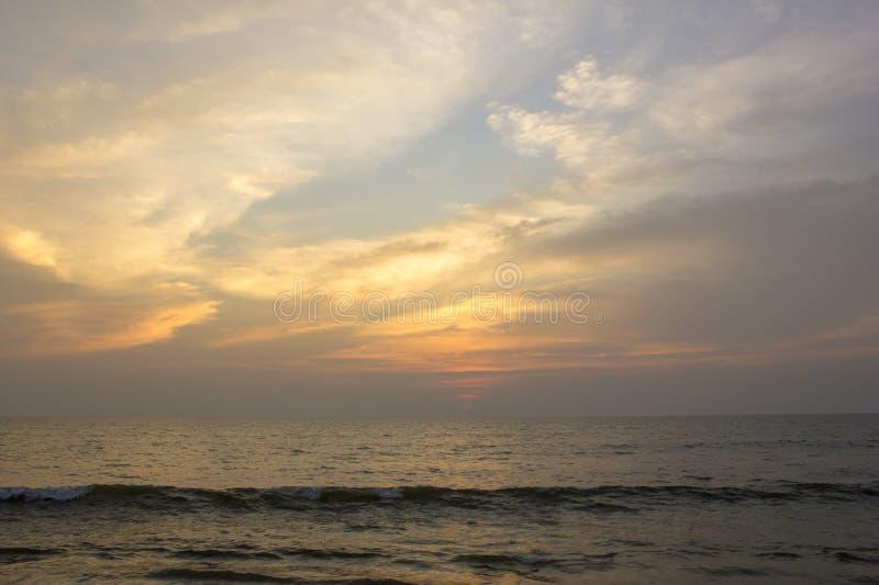 Κύματα θάλασσας ενάντια σε έναν μπλε και πορτοκαλή ουρανό ηλιοβασιλέματος στοκ φωτογραφία με δικαίωμα ελεύθερης χρήσης