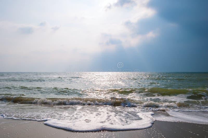 Κύματα θάλασσας σε μια αμμώδη παραλία με το θυελλώδη ουρανό στοκ εικόνες