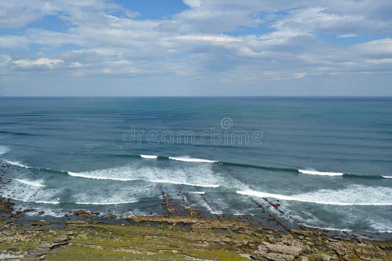 Κύματα θάλασσας στην ακτή της Πορτογαλίας σε μια ηλιόλουστη νεφελώδη ημέρα στοκ εικόνες