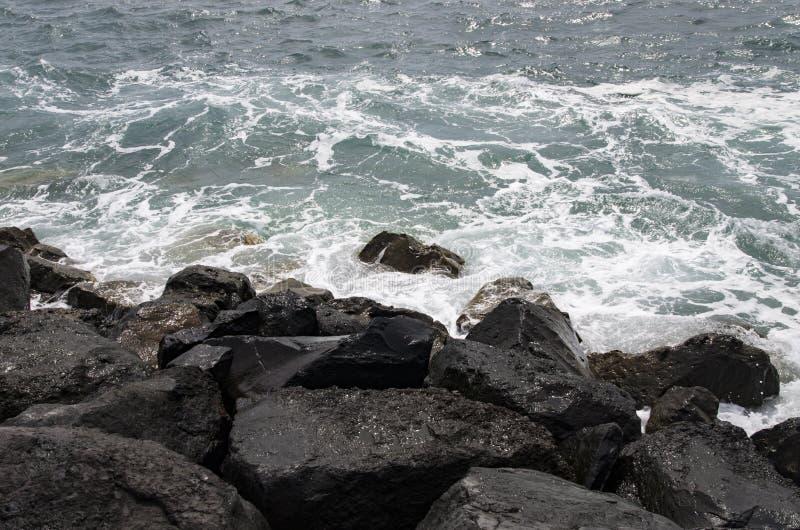 Κύματα κυματωγών που οργανώνονται στους μαύρους φραγμούς πετρών στοκ φωτογραφίες