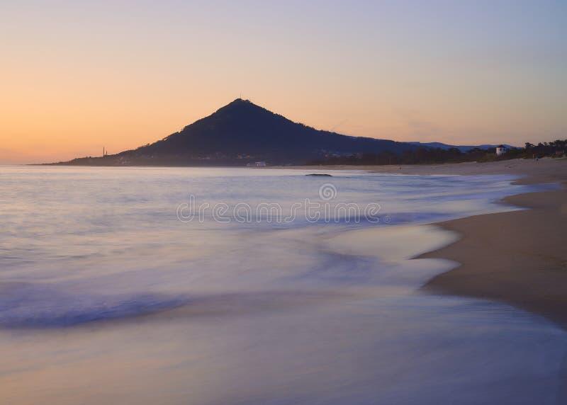 Κύματα πέρα από μια αμμώδη παραλία στο ηλιοβασίλεμα με το βουνό στο υπόβαθρο στοκ φωτογραφία με δικαίωμα ελεύθερης χρήσης