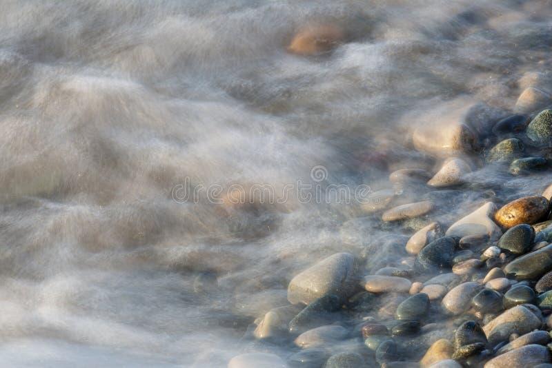 Κύματα που ορμούν πέρα από τις πέτρες σε μια Huron λιμνών παραλία στοκ εικόνα
