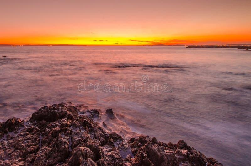 Κύματα που σπάζουν πέρα από τους βράχους στο ηλιοβασίλεμα στη λιμνοθάλασσα Langebaan, Νότια Αφρική στοκ φωτογραφία
