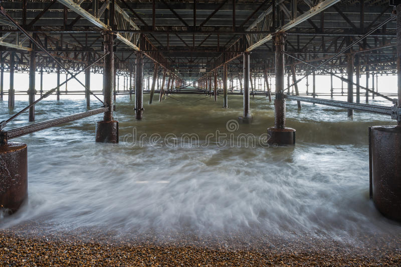 Κύματα που συντρίβουν ενάντια στους στυλοβάτες κάτω από την αποβάθρα Hastings - μακρύς πρώην στοκ εικόνα με δικαίωμα ελεύθερης χρήσης