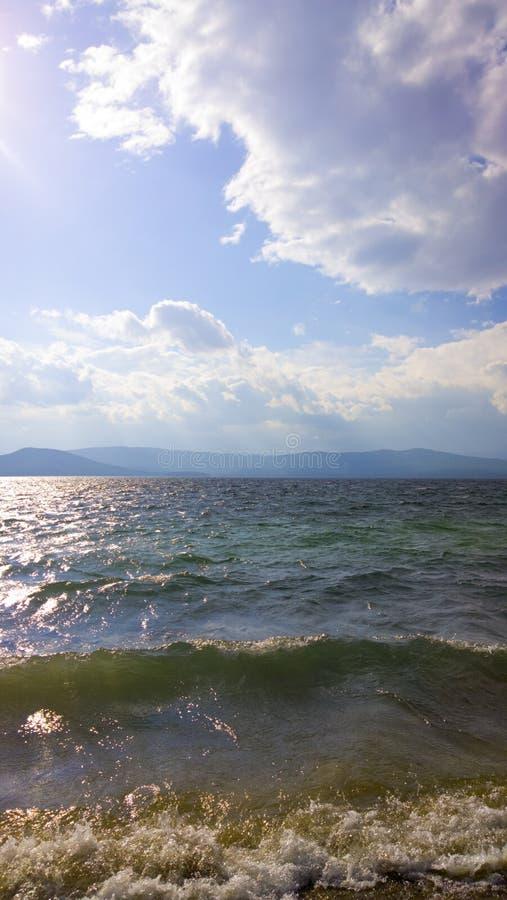 Κύματα στη θάλασσα Θύελλα στη λίμνη Τέλος της θύελλας ενάντια ανασκόπησης μπλε σύννεφων πεδίων άσπρο σε wispy ουρανού φύσης χλόης στοκ φωτογραφία