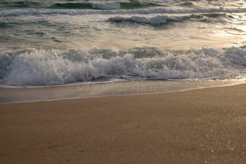 Κύματα της μπλε θάλασσας που καταβρέχει στην αμμώδη ακτή στοκ φωτογραφία