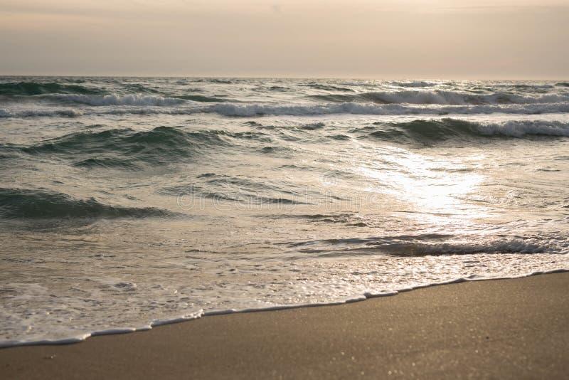 Κύματα της μπλε θάλασσας που καταβρέχει στην αμμώδη ακτή στοκ εικόνες