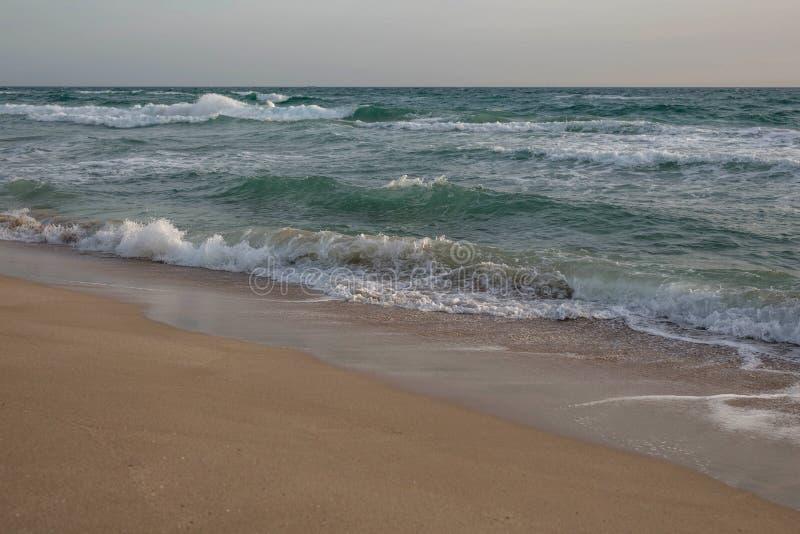 Κύματα της μπλε θάλασσας που καταβρέχει στην αμμώδη ακτή στοκ φωτογραφίες