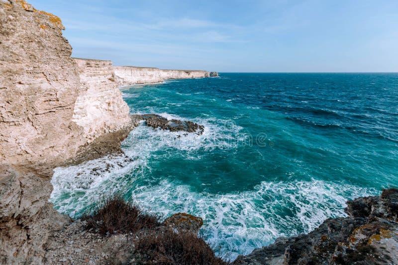 Κύματα του μπλε ραντίσματος θάλασσας στους άμμος-χρωματισμένους απότομους βράχους στοκ εικόνες