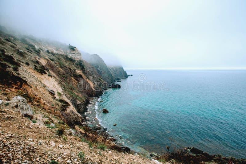 Κύματα του μπλε ραντίσματος θάλασσας στους άμμος-χρωματισμένους απότομους βράχους στοκ φωτογραφίες με δικαίωμα ελεύθερης χρήσης