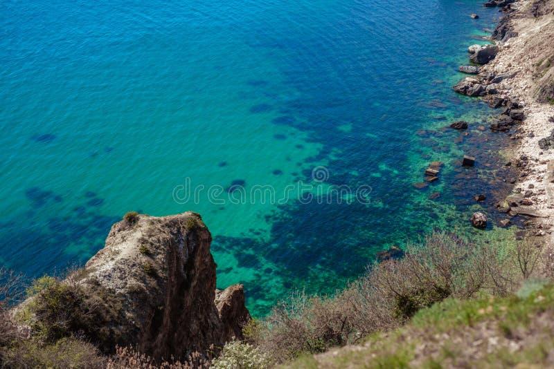 Κύματα του μπλε ραντίσματος θάλασσας στους άμμος-χρωματισμένους απότομους βράχους στοκ φωτογραφίες