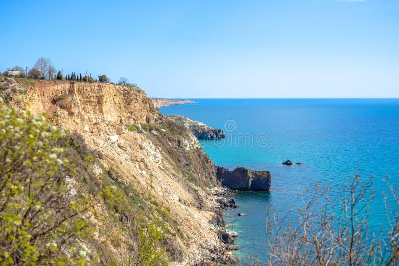 Κύματα του μπλε ραντίσματος θάλασσας στους άμμος-χρωματισμένους απότομους βράχους στοκ φωτογραφία με δικαίωμα ελεύθερης χρήσης
