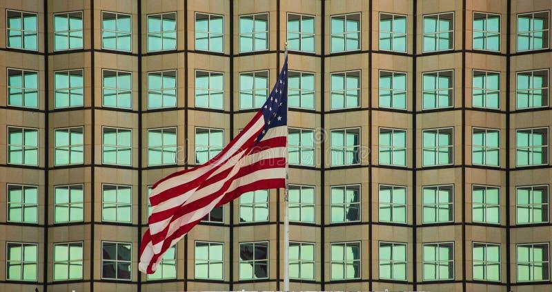 Κύμα αμερικανικών σημαιών σε ένα υπόβαθρο οικοδόμησης στοκ εικόνες