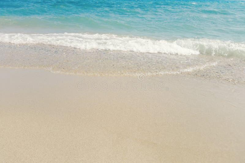 Κύμα του μπλε ωκεανού στο αμμώδες θερινό υπόβαθρο παραλιών στοκ εικόνες
