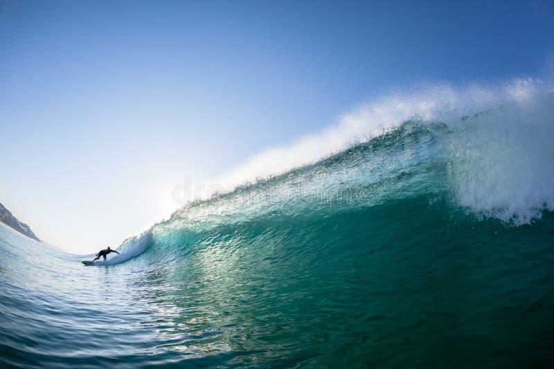 Κύμα Surfer πίσω από την κολύμβηση νερού συντριβής στοκ φωτογραφίες