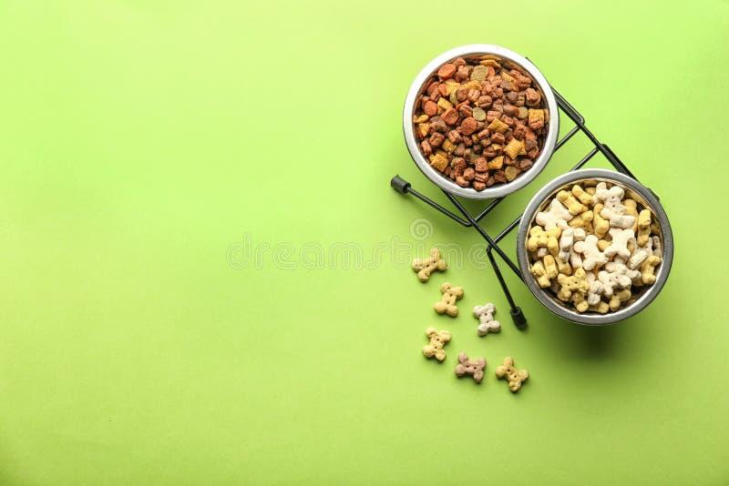 Κύπελλα με τα τρόφιμα κατοικίδιων ζώων στο υπόβαθρο χρώματος στοκ εικόνα με δικαίωμα ελεύθερης χρήσης