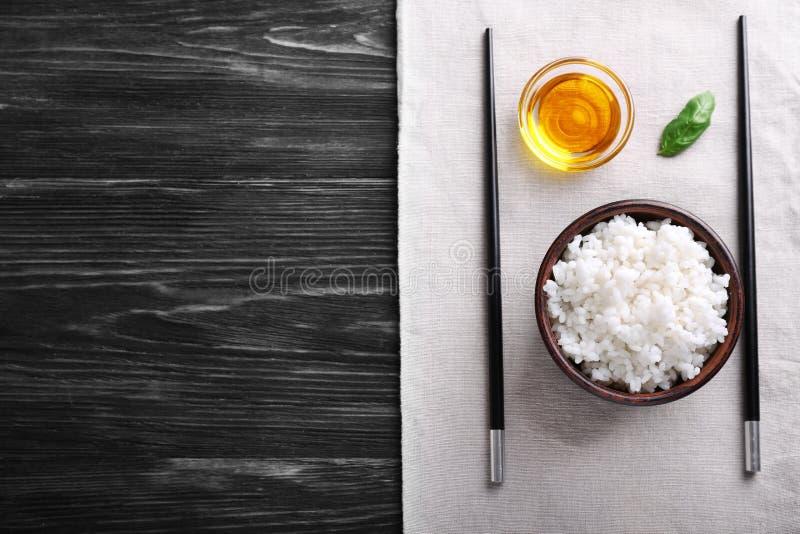 Κύπελλα με το βρασμένα άσπρο ρύζι, το έλαιο και chopsticks στον ξύλινο πίνακα στοκ φωτογραφίες