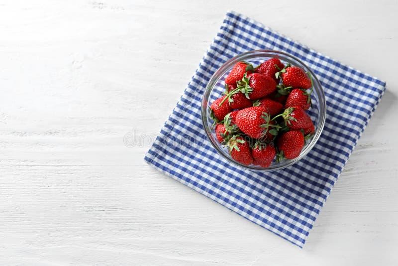 Κύπελλο γυαλιού με τις γλυκές ώριμες φράουλες στον άσπρο ξύλινο πίνακα στοκ φωτογραφία με δικαίωμα ελεύθερης χρήσης