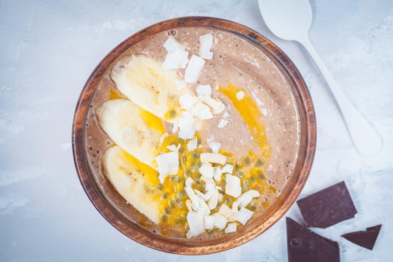 Κύπελλο καταφερτζήδων με τη σοκολάτα, την μπανάνα, την καρύδα και το λωτό στοκ εικόνα