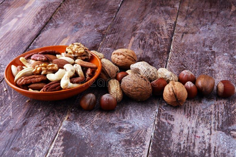 Κύπελλο με τα μικτά καρύδια στο ξύλινο υπόβαθρο Υγιή τρόφιμα και snac στοκ εικόνα με δικαίωμα ελεύθερης χρήσης