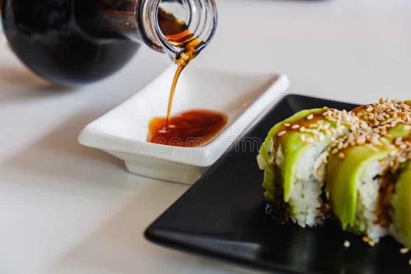 Κύπελλο με τη νόστιμη σάλτσα σόγιας Ρόλος σουσιών με το χέλι και το αβοκάντο ιαπωνικό γεύμα παραδοσι&alpha στοκ φωτογραφίες με δικαίωμα ελεύθερης χρήσης