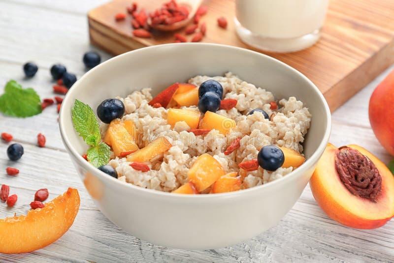 Κύπελλο με oatmeal, τα ροδάκινα και τα μούρα στοκ εικόνες