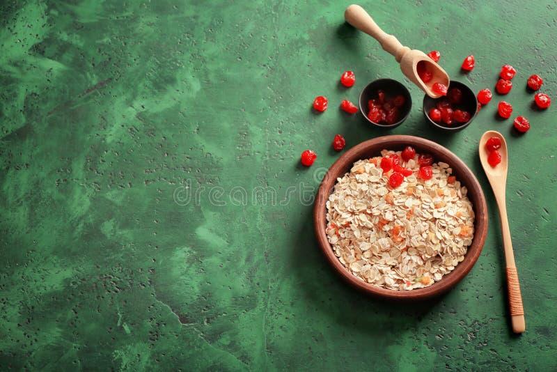 Κύπελλο με oatmeal τις νιφάδες και τα ξηρά μούρα στον πίνακα στοκ εικόνες