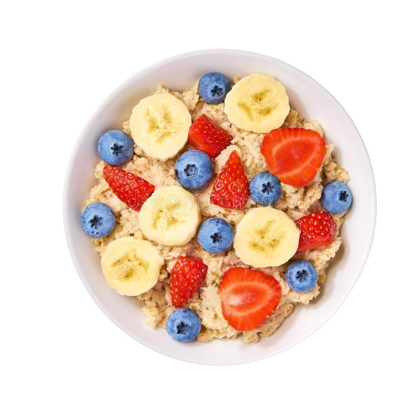 Κύπελλο σπιτικό oatmeal με τα μούρα, την μπανάνα, το βακκίνιο και τη φράουλα στο άσπρο υπόβαθρο που απομονώνεται r στοκ εικόνες
