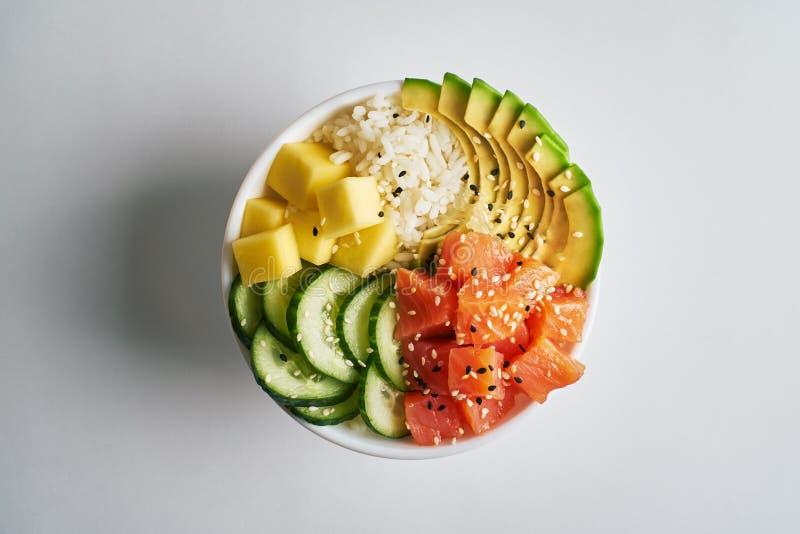 κύπελλο σπρωξίματος με το σολομό, αβοκάντο, μάγκο, ρύζι, αγγούρια, που ψεκάζονται με το άσπρο και μαύρο σουσάμι που απομονώνεται  στοκ εικόνα