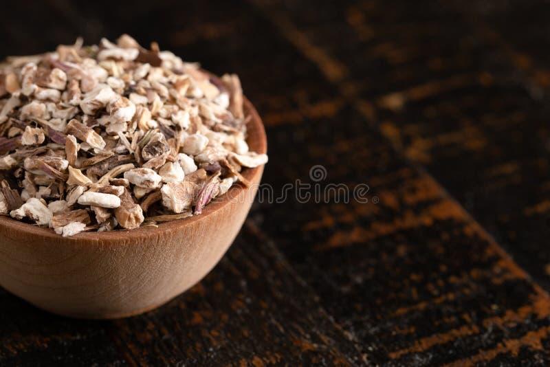Κύπελλο της αφυδατωμένης ρίζας πικραλίδων σε έναν αγροτικό ξύλινο πίν στοκ εικόνα