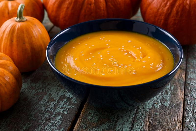 Κύπελλο της πικάντικης vegan σούπας κολοκύθας που διακοσμείται με το φωτεινό πορτοκαλί PU στοκ εικόνες με δικαίωμα ελεύθερης χρήσης