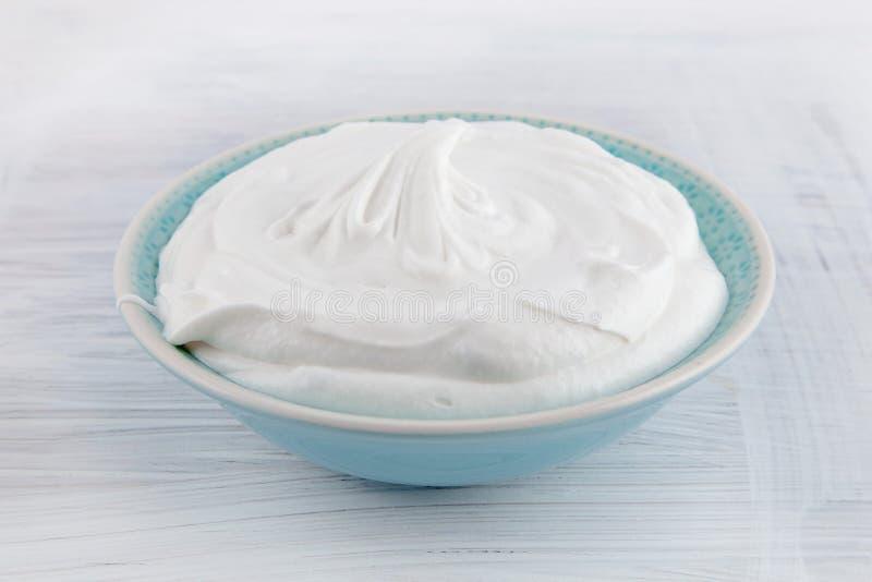 Κύπελλο της φρέσκιας κτυπημένης κρέμας στον άσπρο ξύλινο πίνακα στοκ εικόνες με δικαίωμα ελεύθερης χρήσης