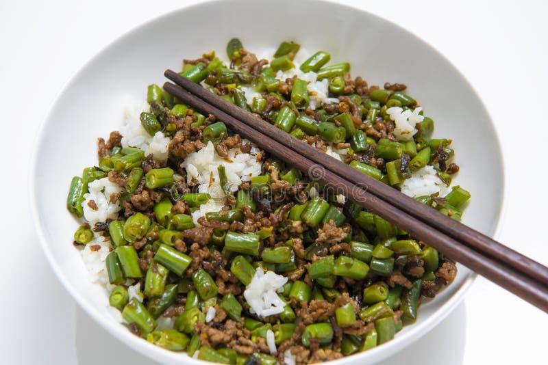 Κύπελλο του κομματιασμένου βόειου κρέατος με τα στρογγυλά φασόλια και το ρύζι, με chopsticks στο άσπρο υπόβαθρο στοκ εικόνα