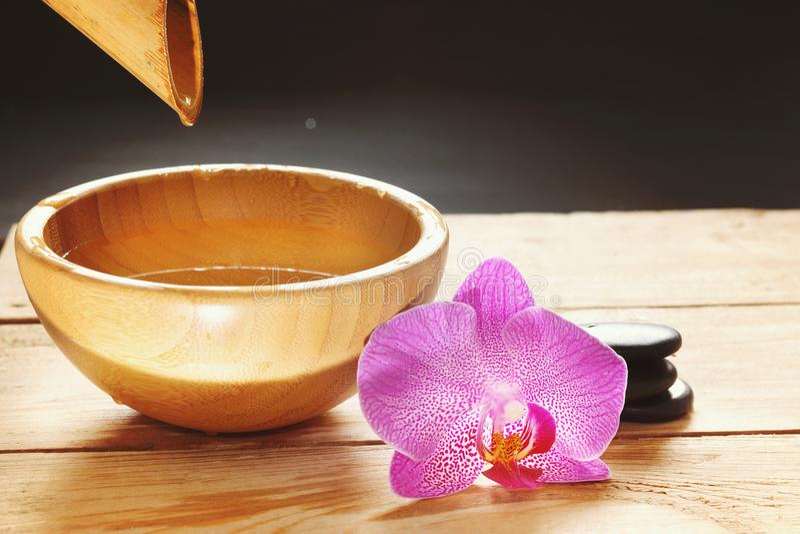 Κύπελλο, το οποίο χύνει το νερό από το μίσχο μπαμπού, τα λουλούδια ορχιδεών και τις πέτρες για ένα καυτό μασάζ σε έναν ξύλινο πίν στοκ εικόνες