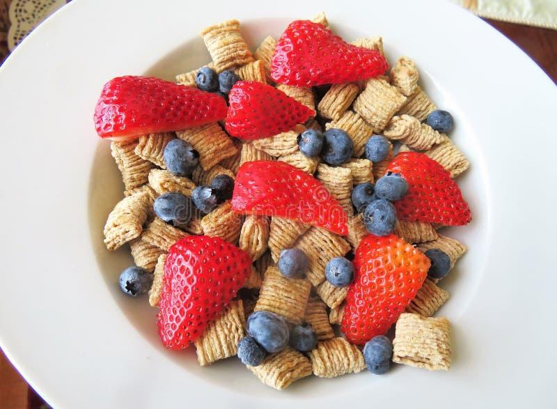 Κύπελλο των δημητριακών με τα φρέσκες βακκίνια και τις φράουλες για ένα θρεπτικό πρόγευμα στοκ εικόνες