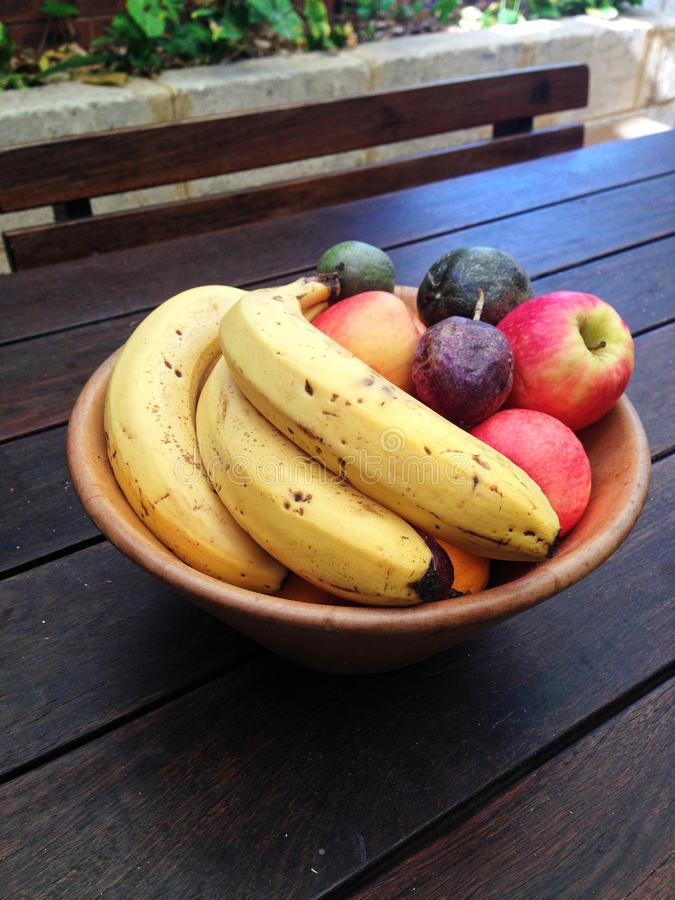 Κύπελλο των φρούτων συμπεριλαμβανομένων των μπανανών, των μήλων και του λωτού σε έναν υπαίθριο ξύλινο πίνακα στοκ εικόνα