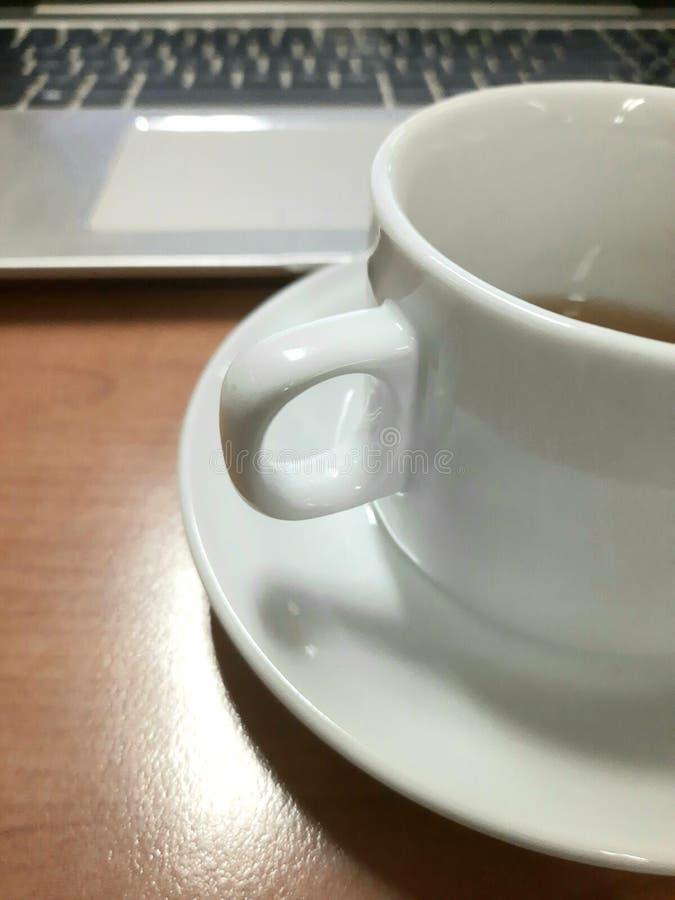 Κύπελλο Tee στο γραφείο και στο φορητό υπολογιστή στο παρασκήνιο στοκ εικόνα με δικαίωμα ελεύθερης χρήσης