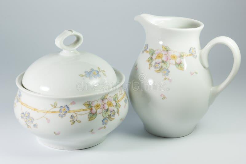 Κύπελλο ζάχαρης και κανάτα γάλακτος με τα λουλούδια στο άσπρο υπόβαθρο στοκ εικόνες με δικαίωμα ελεύθερης χρήσης