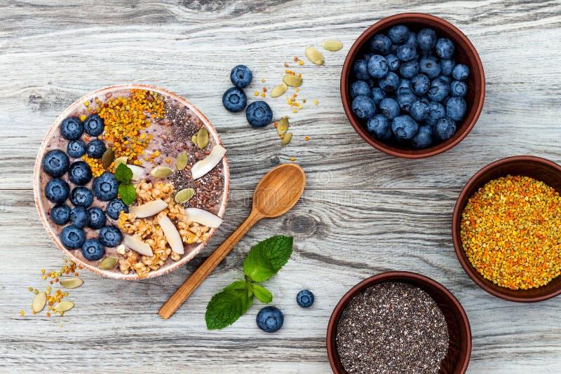 Κύπελλο καταφερτζήδων προγευμάτων Acai superfoods που ολοκληρώνεται με το chia, τους σπόρους λιναριού και κολοκύθας, τη γύρη μελι στοκ φωτογραφίες με δικαίωμα ελεύθερης χρήσης