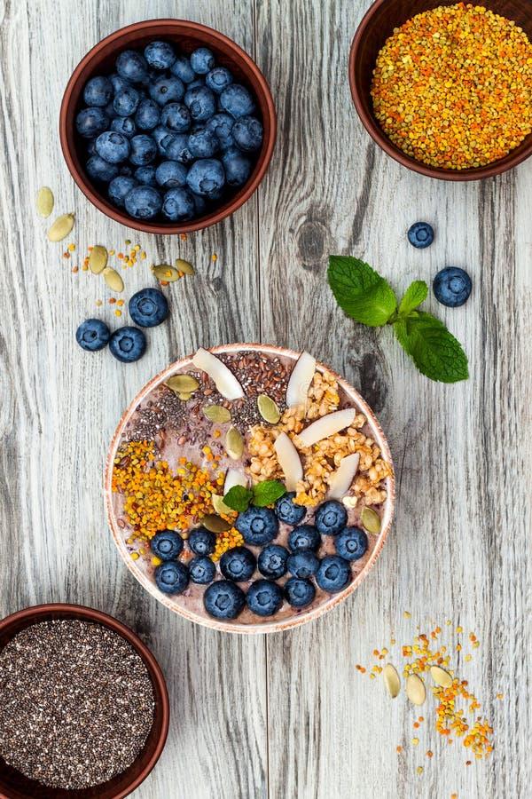 Κύπελλο καταφερτζήδων προγευμάτων Acai superfoods που ολοκληρώνεται με το chia, τους σπόρους λιναριού και κολοκύθας, τη γύρη μελι στοκ εικόνα
