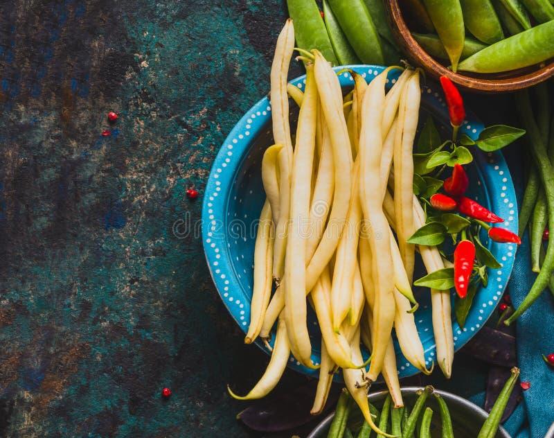 Κύπελλο με τους άσπρους λοβούς φασολιών και τα μαγειρεύοντας συστατικά στο αγροτικό υπόβαθρο στοκ εικόνα με δικαίωμα ελεύθερης χρήσης