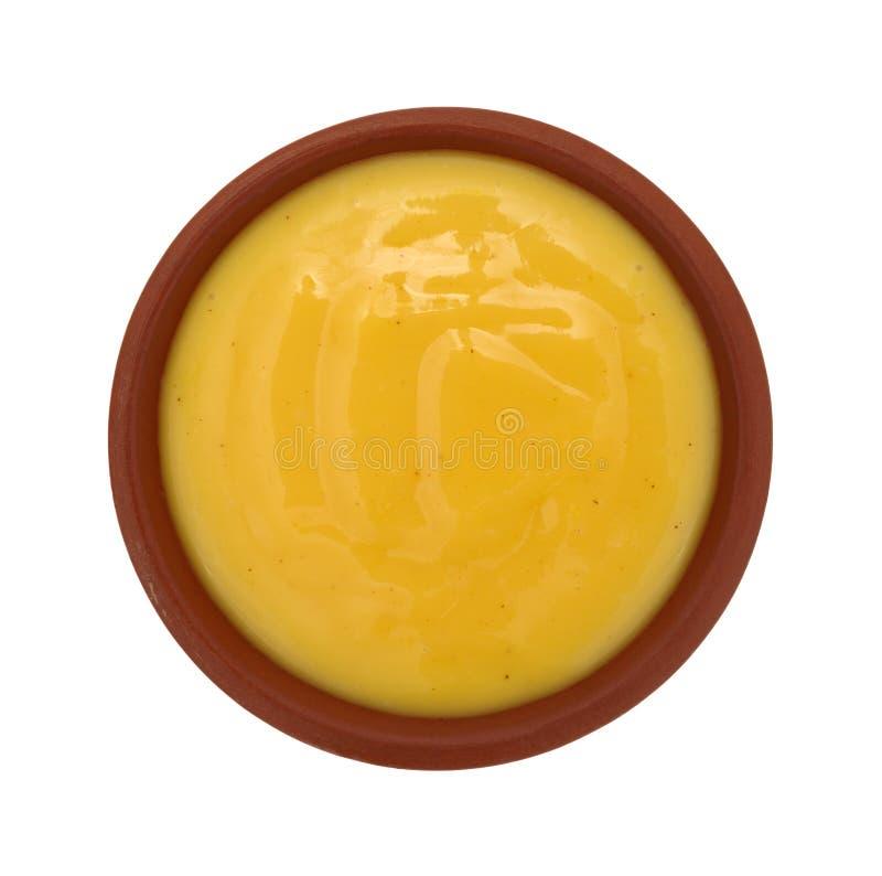 Κύπελλο της μουστάρδας μελιού που ντύνει σε ένα άσπρο υπόβαθρο στοκ εικόνα