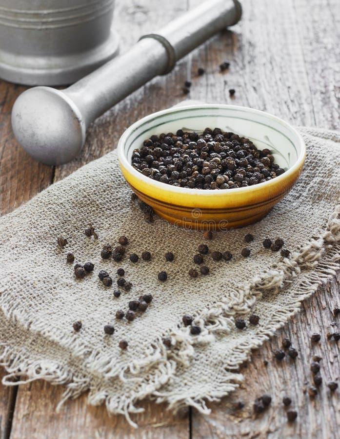 Κύπελλο του μαύρου πιπεριού στον ξύλινο πίνακα στοκ εικόνες με δικαίωμα ελεύθερης χρήσης