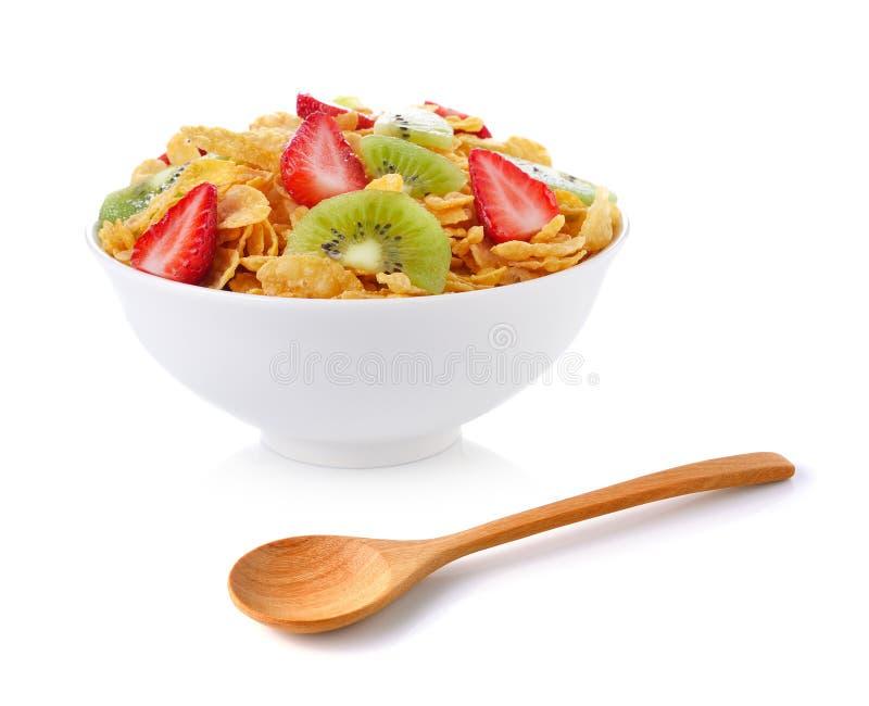 Κύπελλο των νιφάδων καλαμποκιού με τα φρούτα και το ξύλινο κουτάλι στοκ εικόνες