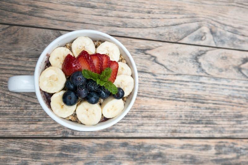Κύπελλο Acai με φραουλών, βακκινίων, μπανανών και peppermint νωπών καρπών τα φύλλα στην κορυφή στον ξύλινο πίνακα στοκ εικόνα