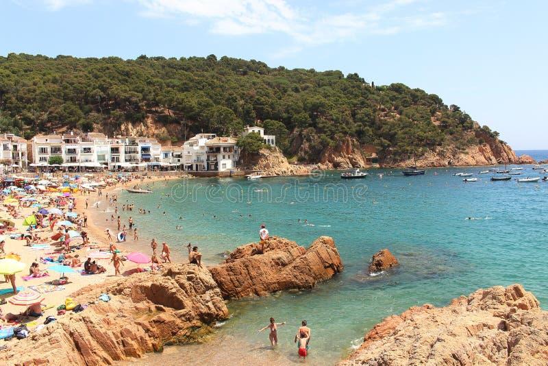 Κύρια άποψη της crowdy παραλίας Tamariu με το χωριό στο υπόβαθρο, Κόστα Μπράβα, Καταλωνία, Ισπανία στοκ φωτογραφία