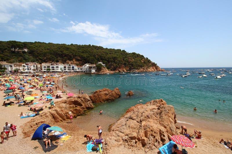 Κύρια άποψη της crowdy παραλίας Tamariu με το χωριό στο υπόβαθρο, Κόστα Μπράβα, Καταλωνία, Ισπανία στοκ εικόνα με δικαίωμα ελεύθερης χρήσης
