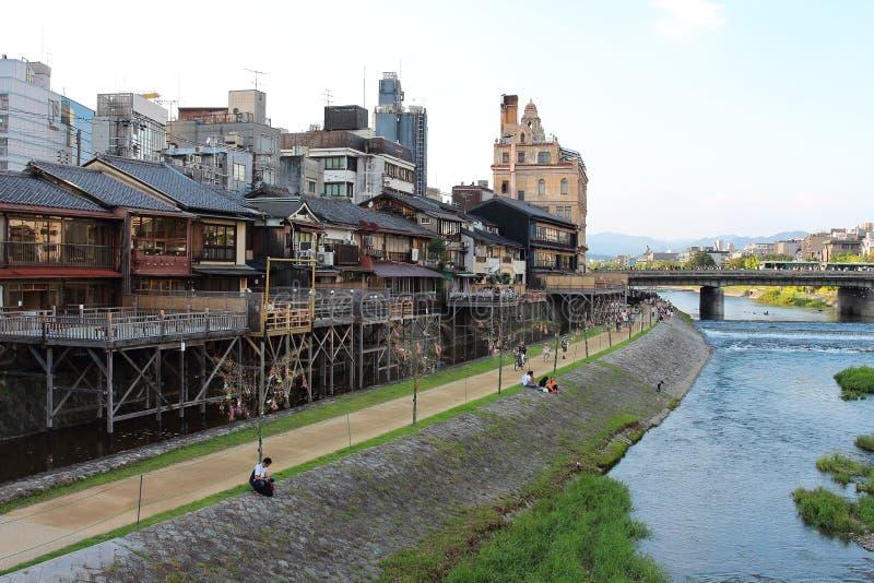 Κύρια άποψη του περιπάτου ποταμών Kamo με πολλά πεζούλια των εστιατορίων και των φραγμών με τα παλαιά πόλης κτήρια του Κιότο ` s  στοκ φωτογραφία με δικαίωμα ελεύθερης χρήσης