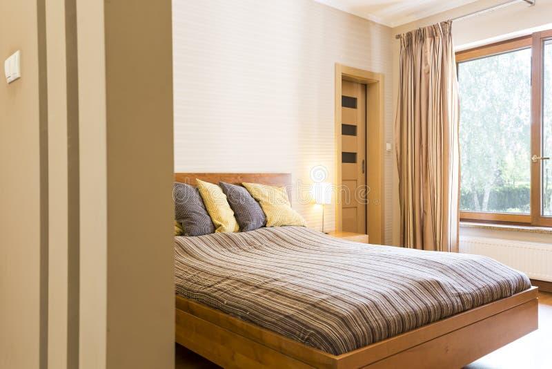 Κύρια κρεβατοκάμαρα με ένα διπλό κρεβάτι με τα μαξιλάρια στοκ φωτογραφία
