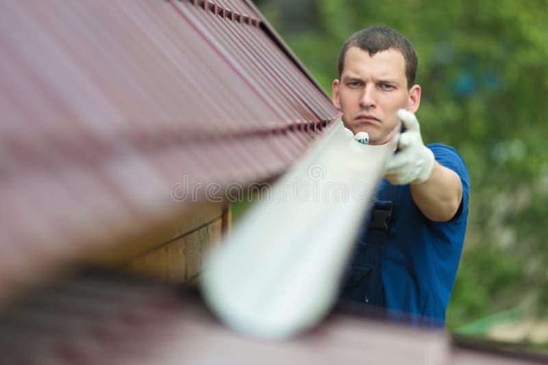 Κύριες επισκευές ο αγωγός στη στέγη, κινηματογράφηση σε πρώτο πλάνο στοκ εικόνα με δικαίωμα ελεύθερης χρήσης
